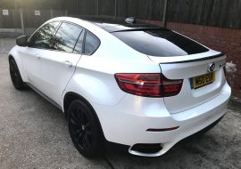 A wrapped pearl white BMW X6M